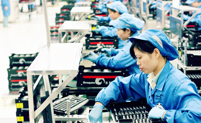 Three workers arranging circuit boards in a tray at workstations in the Seagate factory in China.