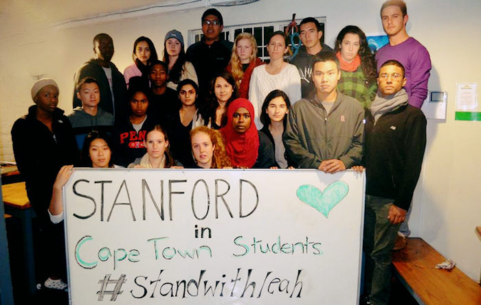 About two dozen students standing in a group holding a sign that says Stanford in Cape Town Students #standwithleah.