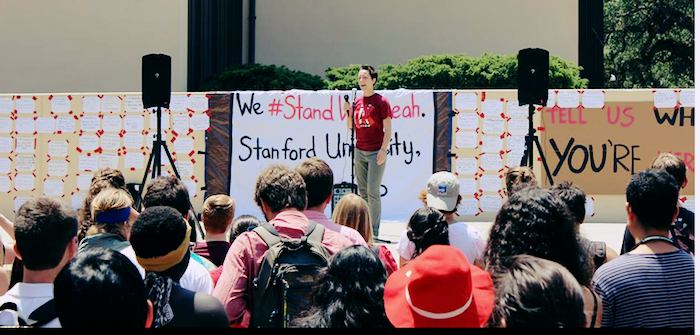 A rally for #standwithleah at Stanford. A student addresses a gathering, holding a microphone.