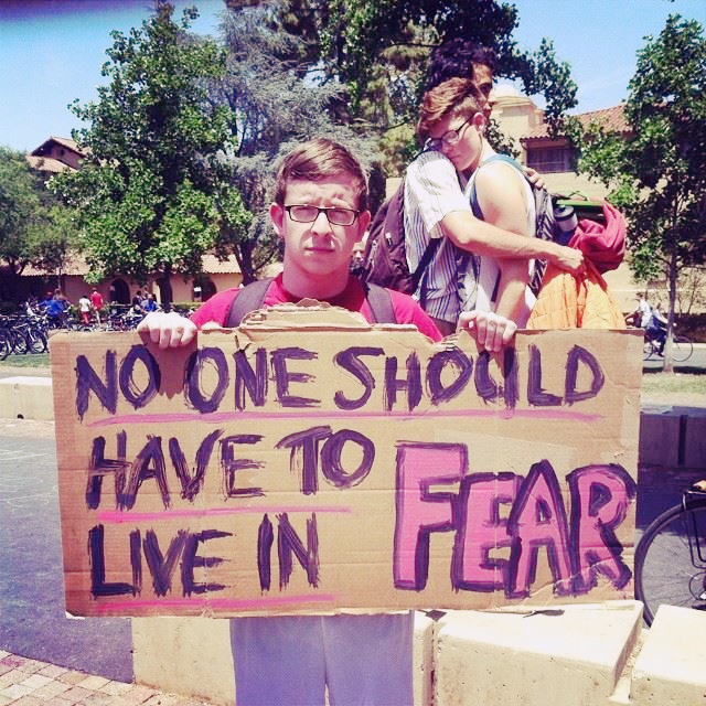 A student holds a sign that says No One Should Have to Live in Fear. Two students embrace in the background.