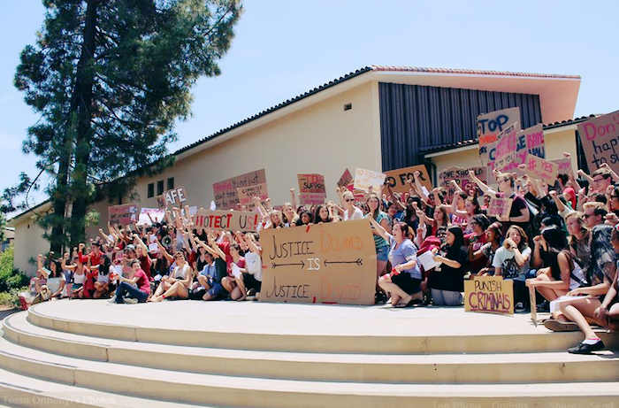 A large group of students gathers on steps, holding signs and lifting their hands in the air. The largest sign reads Justice Delayed is Justice Denied.