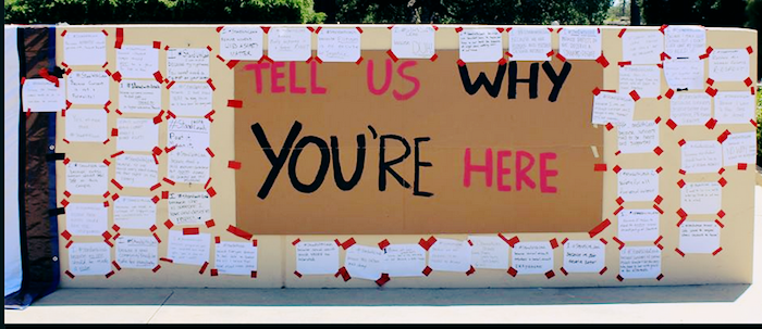 A large wall with a large sign that reads Tell Us Why You're Here with many responses written on paper and taped near it. Specific answers are not legible.