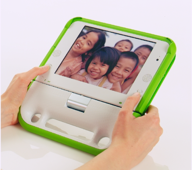 Photo of a computer for the One Laptop Per Child project, a simply designed handheld-device with a photo of smiling children displayed on the monitor.