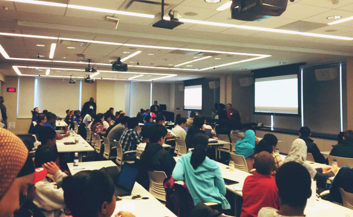 A classroom, with three rows of tables and several projectors, during the youth tech day at Microsoft.