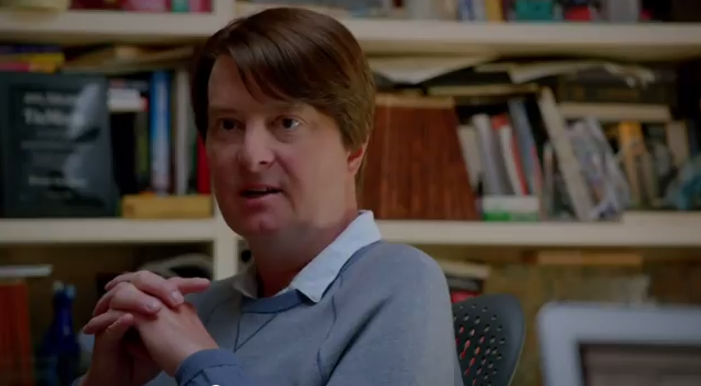 A middle aged white man lectures the viewer about the venture capital deal he is prepared to offer, hands clasped, in an office backed by bookshelves. He is wearing a sweater over a button down.