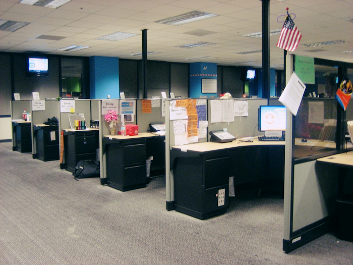 A bleak row of cubicles with assorted office supplies and decorations.