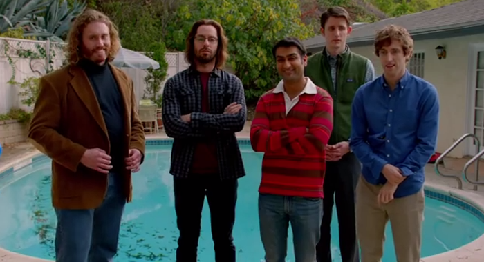 A group of five young men, posing awkwardly in front of a small backyard swimming pool. All are wearing collared shirts. One man wears a professor style blazer, with elbow patches, another has a Patagonia fleece vest.