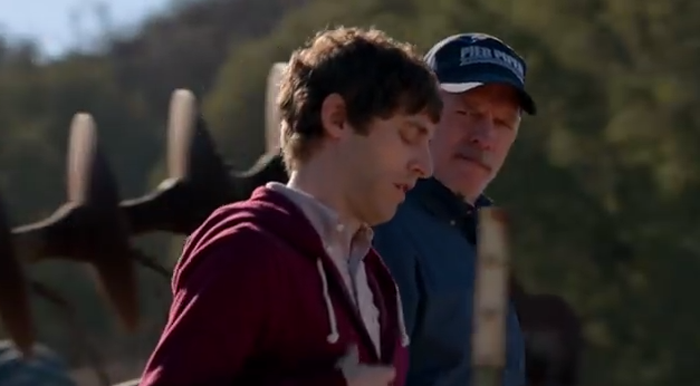 A young white man who looks like Mark Zuckerberg, in a collared button down and a hoodie, walks with an older white man wearing a baseball hat. They are walking together outside, a piece of rusted farm equipment is in the background. In the scene the younger man is trying to pitch his startup to the condescending older man.