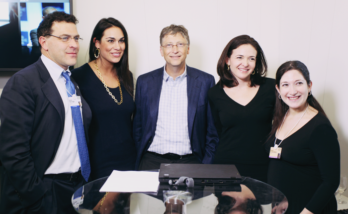 Sandberg, shown posing with Bill Gates and other Facebook employees.