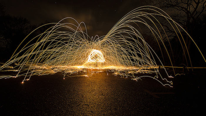 Wire wool spinning in a metal whisk, creating a bright central light with many neon wires emerging from it.