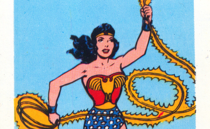 Scan of a Wonder Woman card, showing Wonder Woman running forward, one arm raised holding a golden, electrified rope.