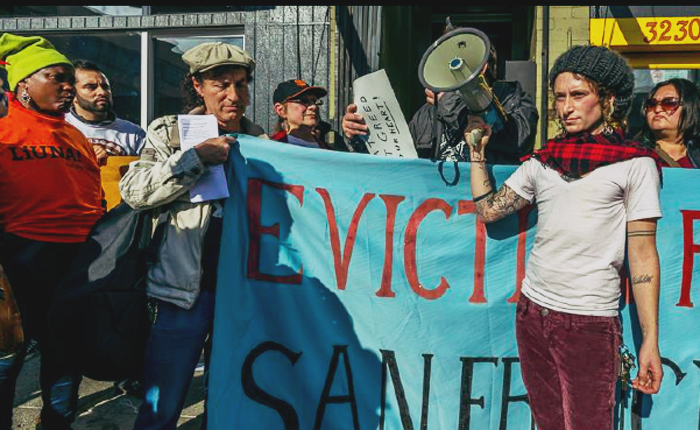 Protesters, with a megaphone, hold large fabric banner reading: Eviction Free San Francisco.