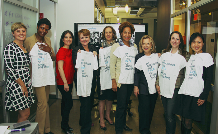 Nine women standing in a hallway posing for a group photo. They are holding up shirts that say 'This is what an angel looks like' and 'Changing the face of angel investing'