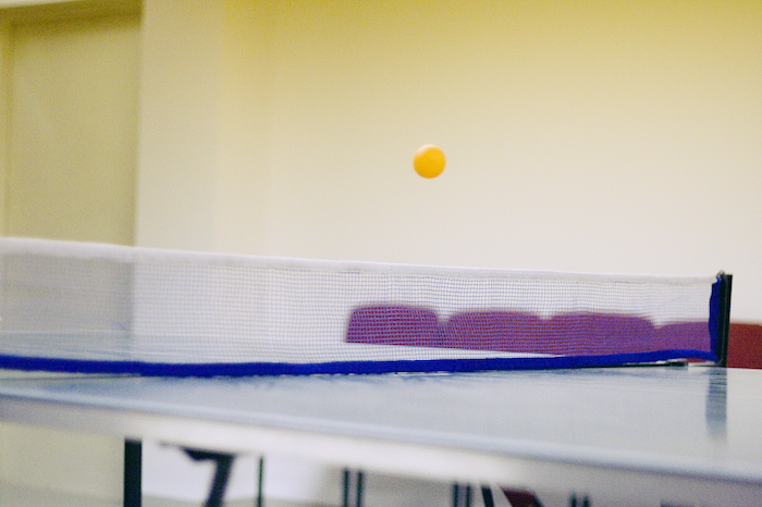A pingpong table with a plastic ball caught in mid-traverse.