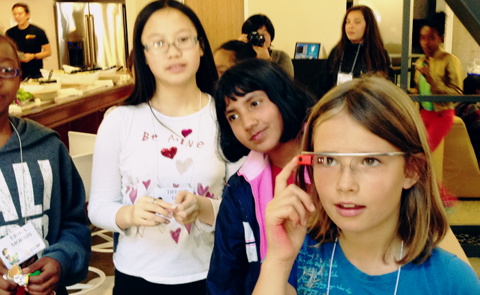 Photo of four girls who are participating in the University of San Francisco summer computer science program. The girl nearest the camera is having her turn trying on the Glass and appears immersed in looking at the tiny screen of the glass, grinning slightly, as she taps the button on the side.