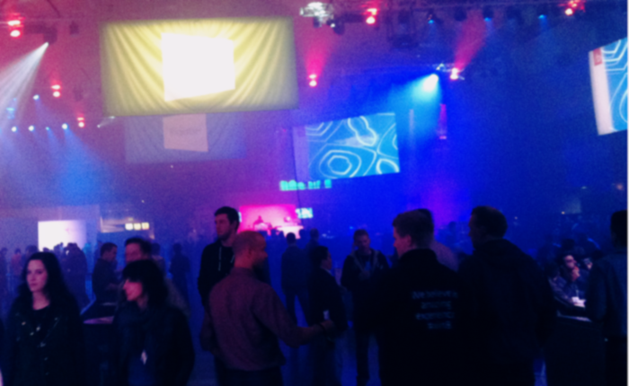 Photo of a large conference hall space, bathed in spotlights and haze. Fabric screens hang from the ceiling, with unintelligible things projected on them. On the floor, shadowy figures, mostly wearing dark clothing, are mingling in small groups.
