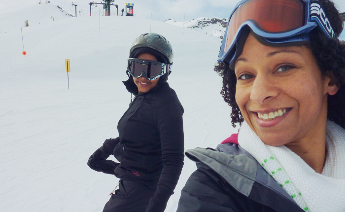 Photo of the author and her new friend Anisha, on a snowy slope. Anisha is grinning, wearing a helmet and goggles, as she turns to face the camera. Richards, with her goggles on her head, is also grinning. In the background there are a few marker flags and a ski lift.