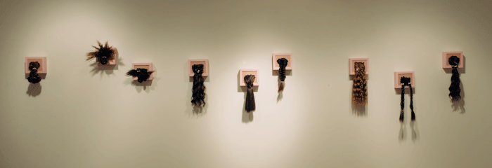 White art gallery wall, with nine pink picture frames. The frames are filled with pink silicon, and a variety of ponytails and hair are hanging down from the frames to be styled by the visitor to the gallery.