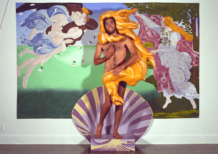 Photograph of the Vensusification installation, showing an Audience member participating by standing on a large painted purple shell in front of a mockup of Botticelli's 'The Birth of Venus' and wearing a golden paper maché  wig and nothing else.