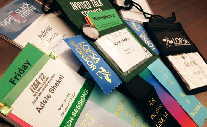 An array of about ten badges spread across the table. Many have ribbons and special tags on them that say 'invited speaker'.