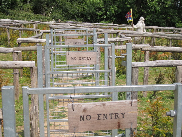 A photo of a series of wooden fences, each saying 'no entry'. A statue of a yeti is in the distant right corner beyond the fences.