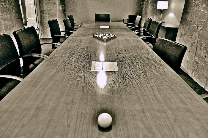 A long conference table in a board room.
