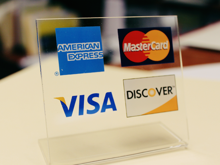 Image of a tabletop sign with credit card logos on it.
