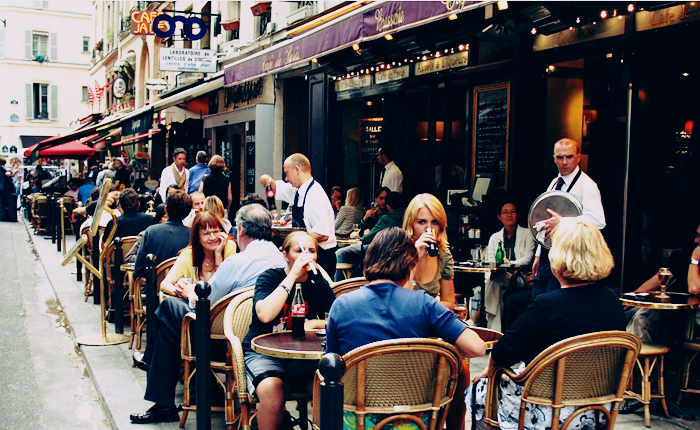 A french cafe scene, with many tables close together with different parties packed into the sidewalk seating area.