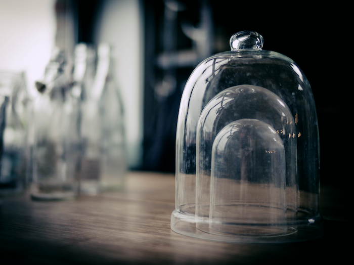 A series of three belljars on a wooden table.