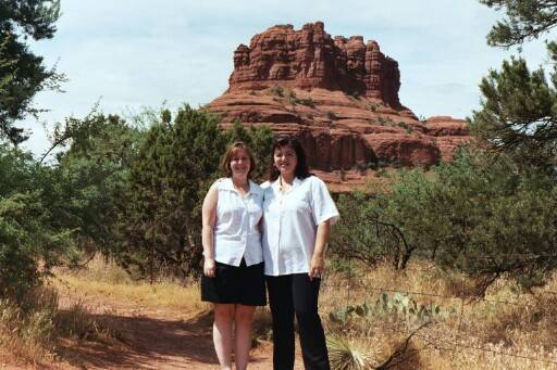 Ginny and Chancey in front of a Sedona rock formation.