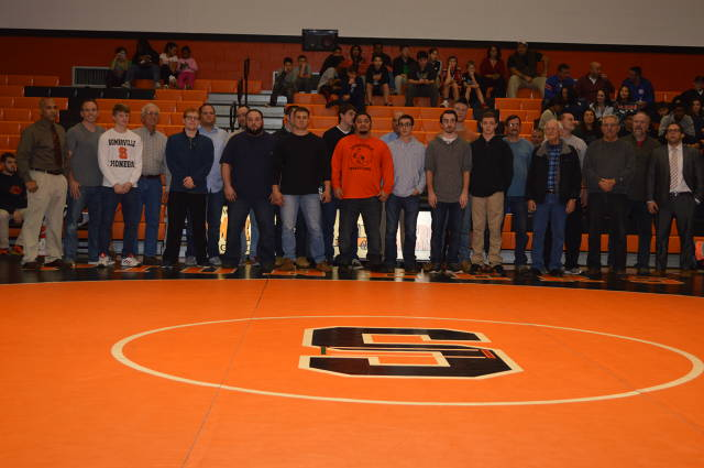 Evan Drill stands to be recognized for his 100th career win with coaches and other alumni