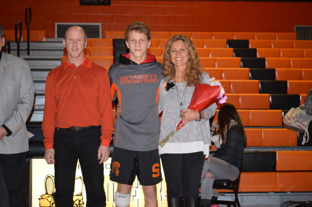 Evan is recognized on senior night with his parents, Barry and Karen.