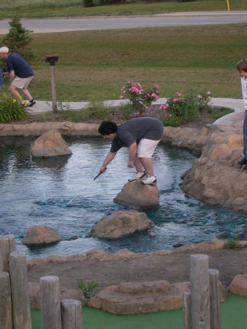 Nat Ahrens does all he can to retrieve his ball in the pond at at Libertyville.