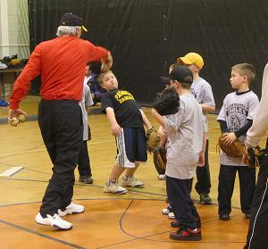2005.  Northeast High School J.V. Coach Tom Caines gives pitching pointers to a group of 8 year olds at Pasadena's winter camp.