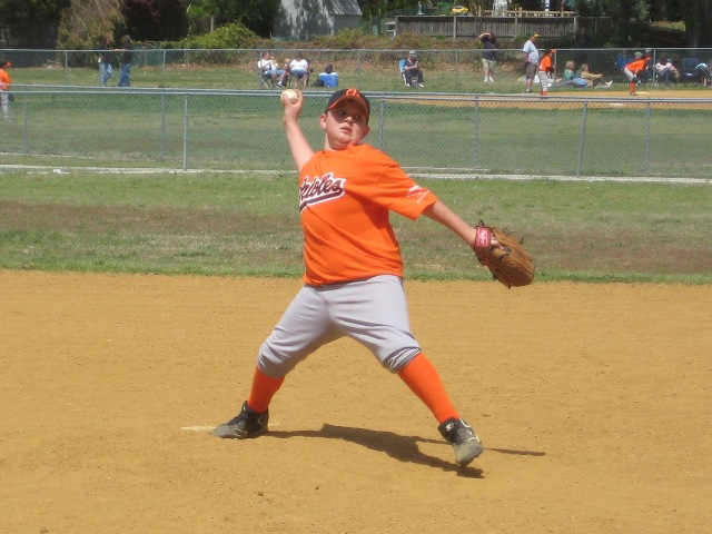 2010. Opening Day on the 12U field: TJ Ratliff reaches back to fire one in.