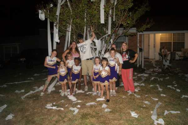 The girls with Coach Mike of the Flag Football team after they rolled his house.