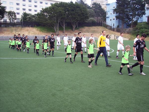 Ball boys, Seals, and Blue Stars march onto the field.