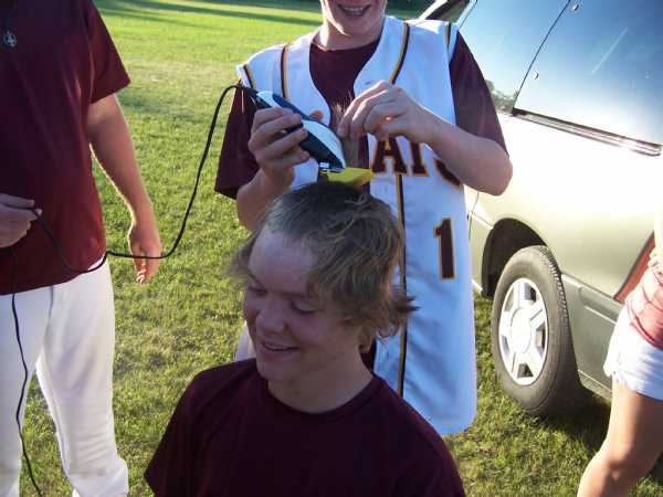 The younger Funk brothers cutting off Brenen Brockpahler's hair at the ballpark right after the game.  Anyone who got a hit in the game got to cut a chunk off.