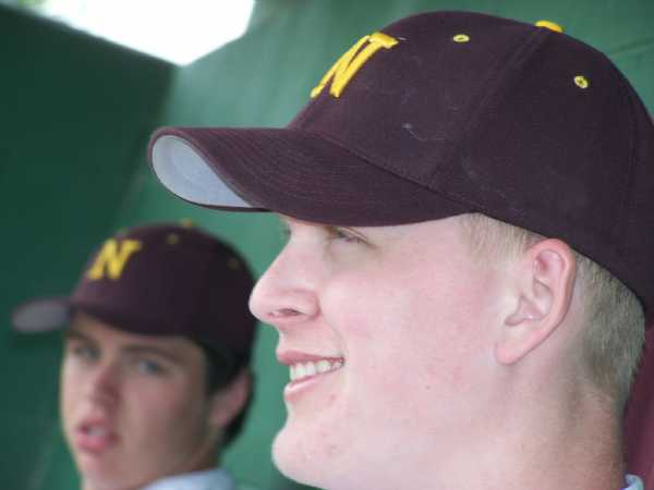 Jake Sumner and Travis Titcomb taking in the action from the dugout during a home game.