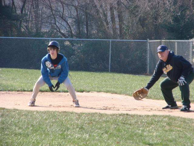Marlton Braves' John Rudman holds a youngster on at first base at Winterball 2010