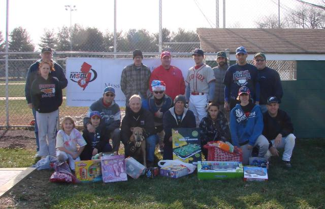 Group Photo of the players who finished the game at Winterball 2010 posing with some of the toys collected