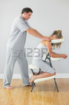 Masseur-treating-shoulders-of-client-in-massage-chair-in-bright-room