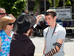 An Orthodox Jewish man helping a Jewish youth (Lisa Kudrow's son) put on tefillin (phylacteries). (photo creit: Flickr/Robert Couse-Baker/CCBY-SA)