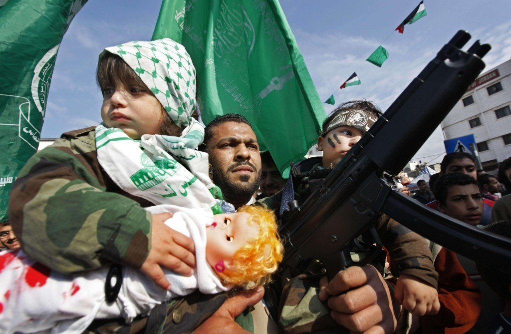 A Hamas militant and his two children participate in a rally in Palestine Square in Gaza City, in the northern Gaza strip, Tuesday, Jan. 20, 2009. U.N. chief Ban Ki-moon inspected the devastation wrought by Israel's onslaught in Gaza on Tuesday, leading a moment of silence at the U.N. headquarters, as the territory's militant Hamas rulers, triumphant at having survived, held victory rallies amid the ruins. (AP Photo/Ben Curtis) Photo Courtesy: http://neoskosmos.com/news/en/Nicolas%20Mottas-Tel%20Aviv-peaceful-solution-Arab-Israeli-conflict