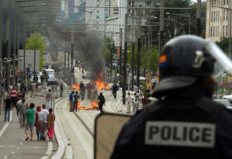A French riot police officer looks at burning barricades along the tramway line in Sarcelles, a suburb north of Paris, on July 20, 2014. (AFP Photo/Pierre Andrieu)