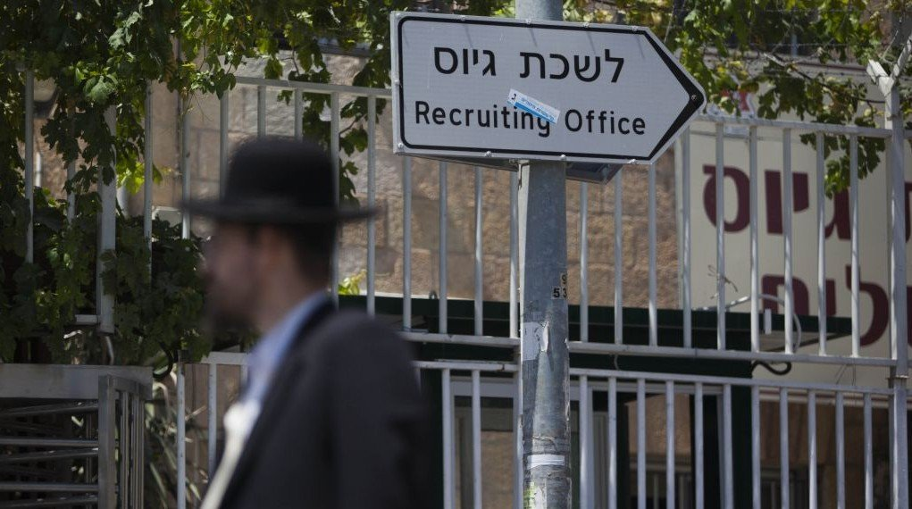 An ultra-Orthodox man walks past the army recruiting office in Jerusalem, July 22, 2013 photo credit: Yonatan Sindel/Flash 90)