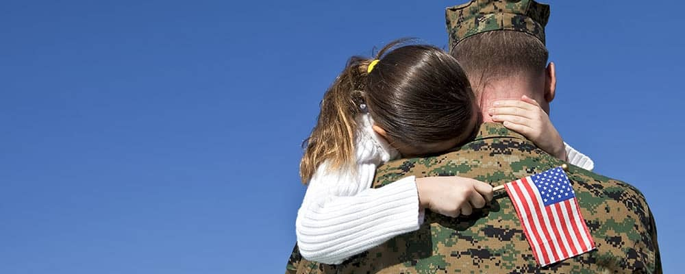 daughter hugging his soldier father while holding a small American flag