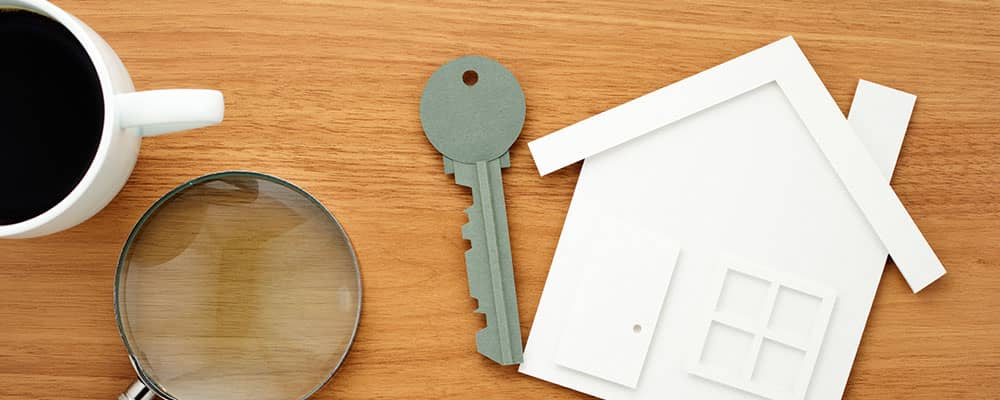 house key, paper house cutout, magnifying glass and coffee cup