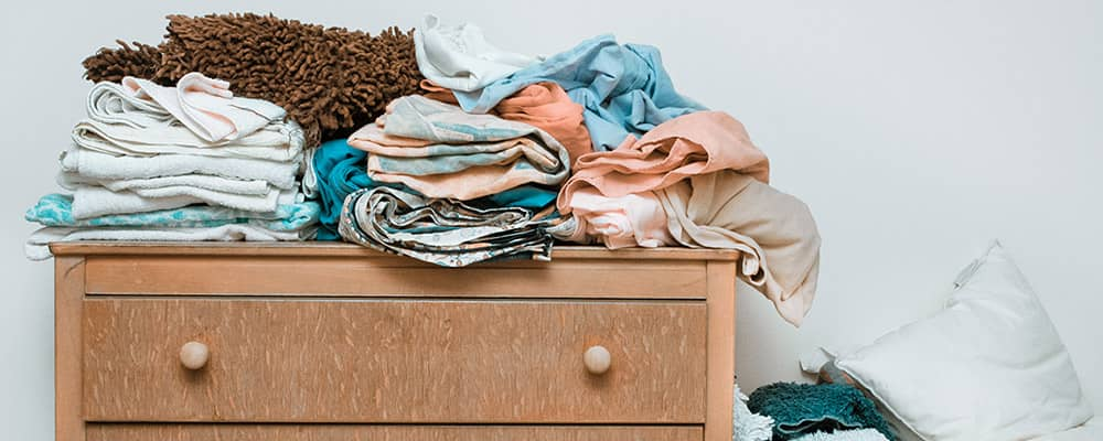 dresser with clothes on folded on top