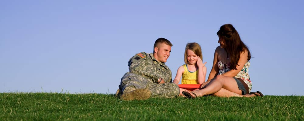 military family sitting together on the lawn